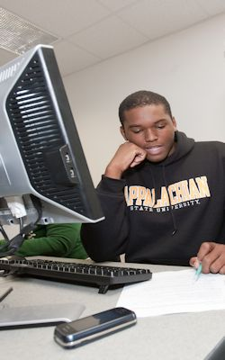 student sitting at a desktop computer